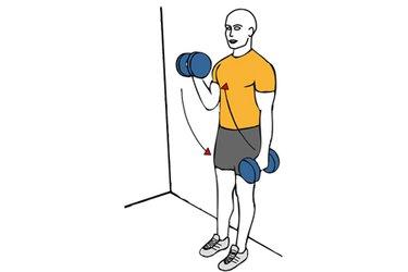 Curl de biceps alterno con mancuernas con giro apoyado en la pared